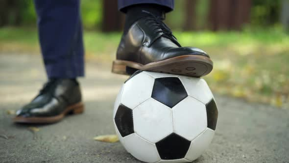Closeup Male Foot in Elegant Leather Shoe Step on Soccer Ball Outdoors