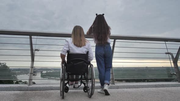 Disabled Mom and Girl Enjoying Landscape on Bridge