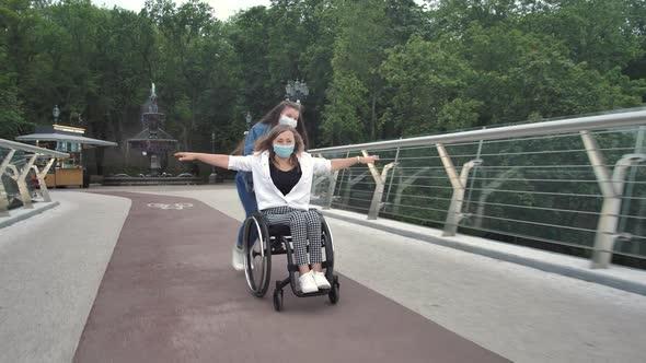 Daughter Driving Mother on Wheelchair Along Bridge