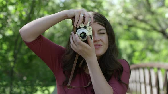 Young woman winding film on camera to take vertical photo