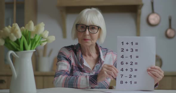 Senior Teacher in Glasses Showing Sheet of Paper with Simple Mathematical Equations Looking