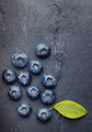 A bunch of delicious blueberries with green leaf on a  black vin - PhotoDune Item for Sale