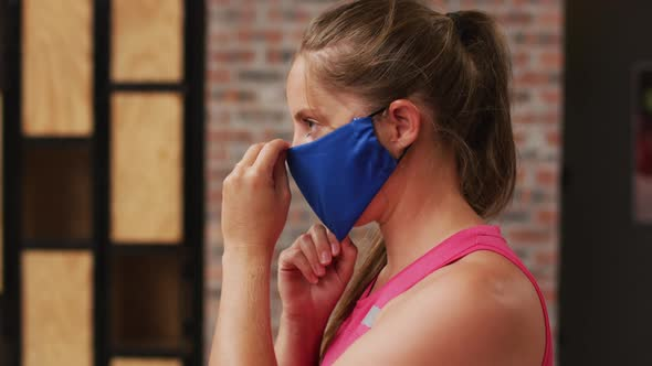 Portrait of caucasian woman at a sports centre adjusting her face mask