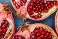 Cut in half pomegranate on a wooden blue surface - PhotoDune Item for Sale
