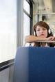 Woman wearing headphones on train - PhotoDune Item for Sale