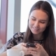 Smartphone Girl Using App On Phone Drinking Coffee Smiling In Cafe.  - VideoHive Item for Sale