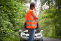 Young female driver wearing a high visibility vest, calling the - PhotoDune Item for Sale