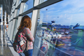 pretty young girl traveler with a backpack next to the panoramic windows - PhotoDune Item for Sale
