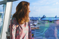 pretty young girl traveler with a backpack next to the panoramic windows of the passenger terminal - PhotoDune Item for Sale