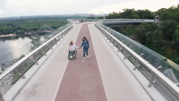 Aerial Shot of Girl Walking with Mom on Wheelchair