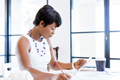 Young woman sitting at a desk in an office and working on blueprint - PhotoDune Item for Sale