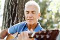 Senior man plying guitar outdoors - PhotoDune Item for Sale