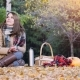 Young Woman Sitting On Picnic Drinking Hot Tea From a Thermos In Autumn Park. Girl Sitting On The - VideoHive Item for Sale