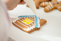 Close up of confectioner hand icing a gingerbread house - PhotoDune Item for Sale