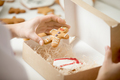 Close up of confectioner hand packing gingerman into a box - PhotoDune Item for Sale