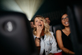 Smiling young women watching movie in theater - PhotoDune Item for Sale