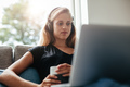 Young woman with headphones looking at laptop - PhotoDune Item for Sale