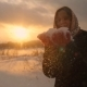 Winter Portrait of a Beautiful Young Woman Blowing Snowflakes and Smiling in  at Magic Sunset - VideoHive Item for Sale