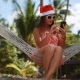 Young Beautiful Woman in Sunglasses and Christmas Hat in Hammock Uses Mobile Phone on Tropical Beach - VideoHive Item for Sale