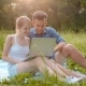 Young Happy Family Looking at Laptop and Laughing in Park with Amazing Sunlight - VideoHive Item for Sale