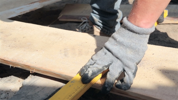 Carpenter Making Measurements and Sawing a Plank
