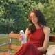 Cute Female Teenager in Dark Red Long Dress and Eyeglasses Drinking Something from Thermo Cup - VideoHive Item for Sale