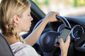 young woman driving and looking at her smartphone - PhotoDune Item for Sale