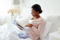 happy pregnant african woman reading book at home - PhotoDune Item for Sale