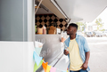 african american man with drink at food truck - PhotoDune Item for Sale