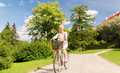 happy senior woman riding bicycle at summer park - PhotoDune Item for Sale