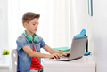 boy with headphones typing on laptop at home - PhotoDune Item for Sale