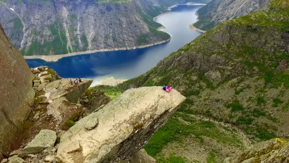 Guy and Girl Sitting on the Edge of the Trolltunga