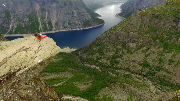 Norway. Guy and Girl Sitting on the Edge of the Trolltunga