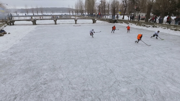 Aerial View of Men Playing Hockey on a Frozen Lake in a City Park in Winter