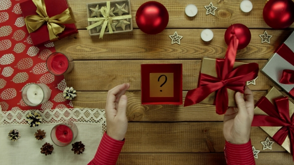 Man Opens Christmas Present with Sticky Note with Question Mark on It, Top Down Shot