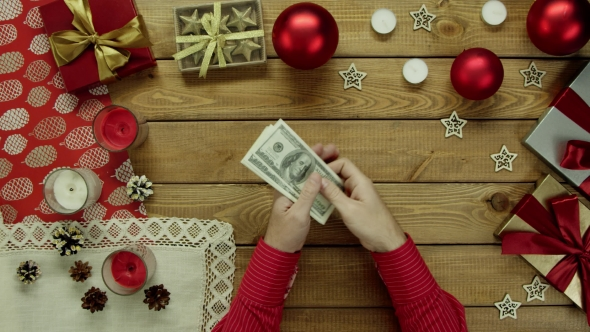 Man Counts Dollars By Christmas Decorated Table, Top Down Shot