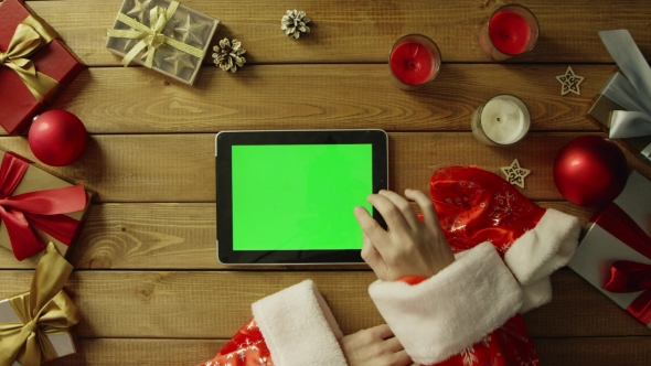 Santa Uses Tablet Pc with Green Screen By Christmas Decorated Table, Top Down Shot