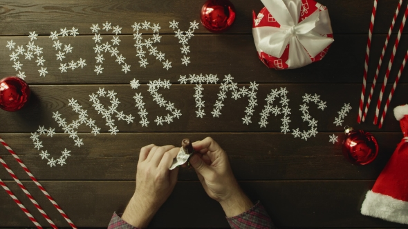 Man Unwraps Candy, Eats It and Throws Wrapper on Christmas Decorated Table, Top Down Shot