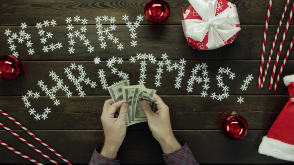 Adult Man Counts Dollars By Xmas Decorated Table, Top Down Shot