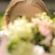 Young Female Plays To the Camera Stare Down Looking Through Flowers Decoration in the Green Magic - VideoHive Item for Sale