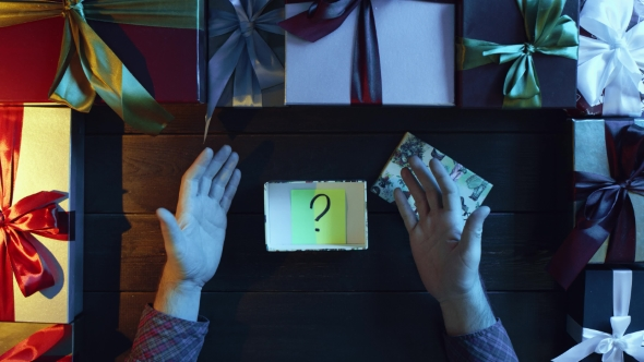 Adult Man Opens New Year Present Box with Sticky Note with Question Mark on It, Top Down Shot