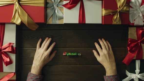 Adult Man Unwraps Candy, Eats It and Throws Wrapper on Christmas Decorated Desk, Top Down Shot