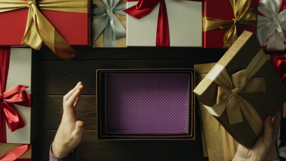 Dissapointed Man Opens Empty Christmas Present Box By Wooden Holiday Table, Top Down Shot
