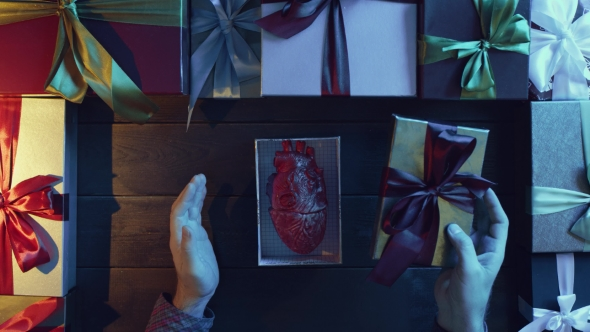 Adult Man Opens New Year Gift Box with Anatomical Human Heart Made of Plastic Inside on Decorated