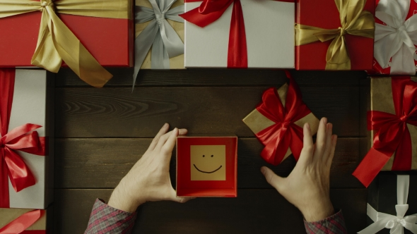Top Down Shot of Adult Man Opening Christmas Present Box with Sticky Note with Smile Inside