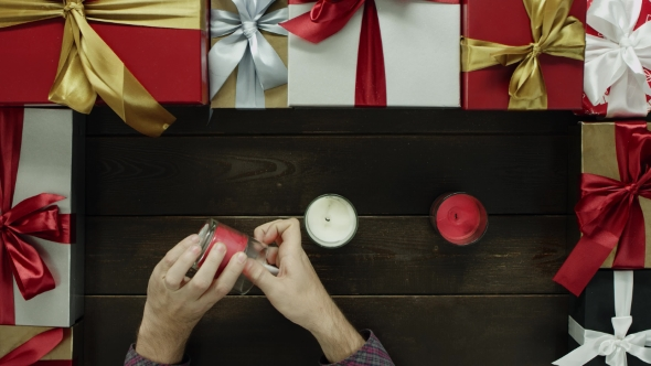 Adult Man Lights Xmas Candles By Decorated Table, Top Down Shot