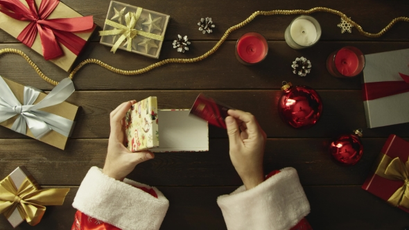 Top Down Shot of Man in Santa Claus Suit Putting Bank Card in Christmas Gift Box By Decorated