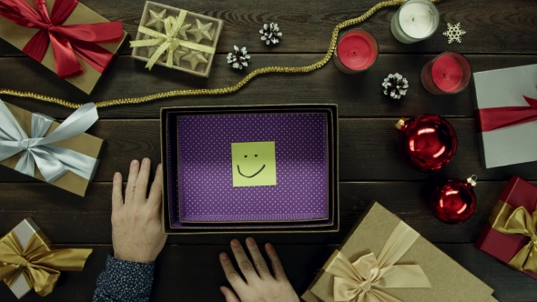 Top Down Shot of Adult Man Unboxing New Year Present Box with Sticky Note with Smile Inside