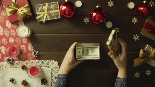Adult Man Opens Christmas Present Box with Dollars Inside, Top Down Shot