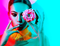 Fashion model woman posing in studio with donut in colorful brig - PhotoDune Item for Sale